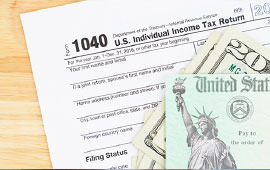 1040 tax form with money sitting on top